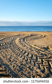 Tractor tracks on the beach, in the sand and into the sea with blue morning sky