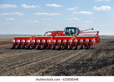 Tractor with trailed planter working in field in a sunny spring day
