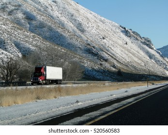Tractor trailer drives cautiously on icy roads  in Eastern Oregon..