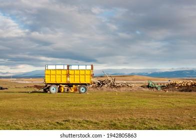 Tractor de remolque, paisaje rural. En el fondo las montañas nevadas.