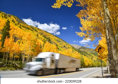 tractor trailer truck driving along Colorado highway on colorful autumn day