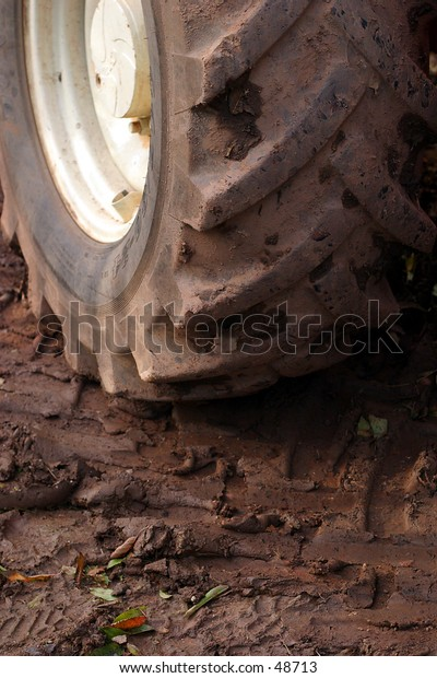 A tractor wheel with a muddy tire.