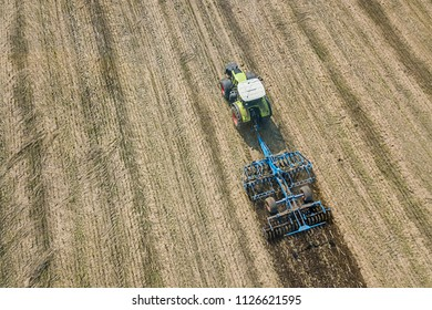 Tractor at work, cultivating a field, Seedbed cultivator Aerial View.