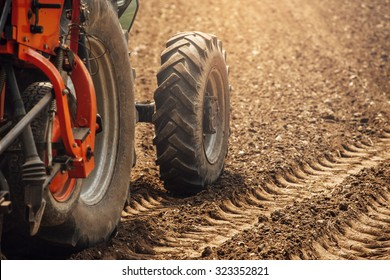 Tractor at work in the fields during a sunny summer day and tracks on the fertile soil