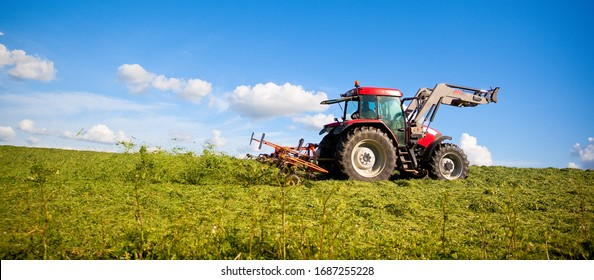Tractor at work in the fields in spring in France.