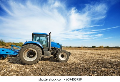 Tractor working in a field, agricultural machinery in the work, agricultural machine cultivates the land, tractor in the background cloudy sky