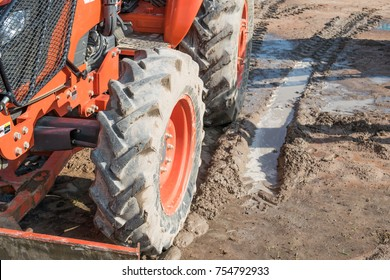 tractor working in a field and tire on the wet mud