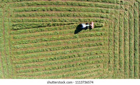 Tractor working in a fields, view from above with drone, mowing grass.
