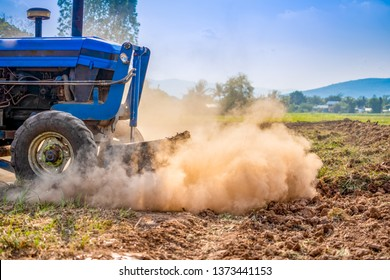 Tractor working on farm agriculture in countryside, tractor plowing grass and soil on hills for improve landscape to seeding plant of rice or other plants