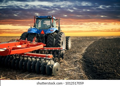 Tractor working on the farm, modern agricultural transport, farmer working in the field, tractor on a sunset background, cultivation of land, agricultural machine