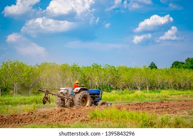 Tractor working on field for planting agriculture, tractor plowing soil land in countryside on seeding season, blue sky and white cloud background and tree forest.