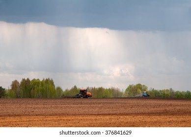 Tractors cultivating the land to prepare the soil for seeding plants