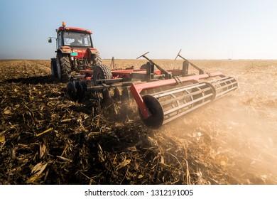 Tractors plowing stubble fields