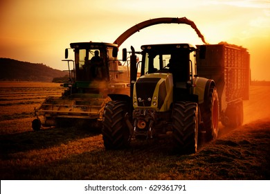 tractors working on farm field at sunset