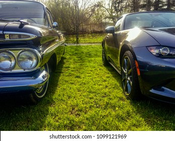 TRACY CITY, TENNESSEE - APRIL 1, 2018: An antique classic 1959 Chevrolet Bel Air is positioned beside a modern sporty 2017 Mazda MX-5 Miata for a visual comparison of young versus old.