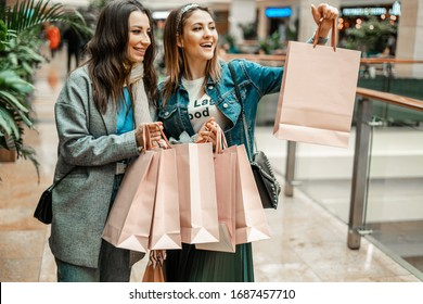 Trade, buyers. Two beautiful girls make purchases in a shopping center, go shopping. The joy of consumption