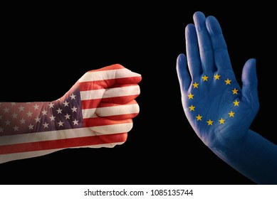 trade conflict, fist with USA flag against a hand with European flag, isolated on a black background