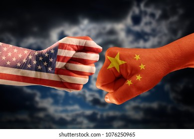 Trade conflict, fists with the flags of USA and China against each other, dramatic sky with clouds in the background
