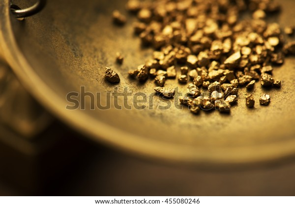 Trade and exchange. Weighing a gold nugget on a old brass scale dish.for trading. Shallow depth of filed.