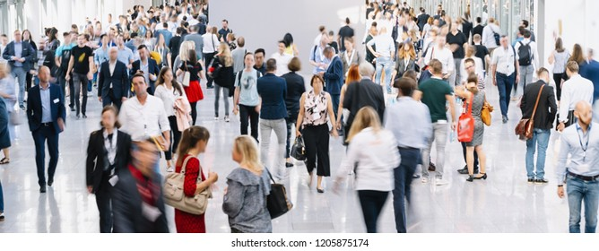 trade fair visitors walking in a clean futuristic corridor