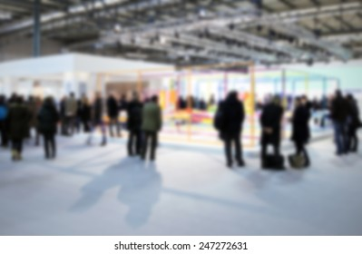 Trade show people. Intentionally blurred post production background.