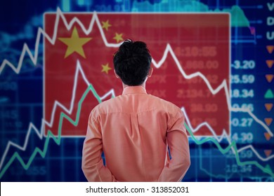 Trade war concept: Young male broker looking at a stock market of china with declining arrows