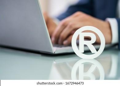Trademark Sign Near Man's Hand Working On Laptop