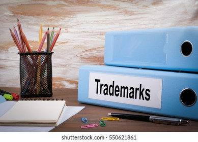 Trademarks, Office Binder on Wooden Desk. On the table colored pencils, pen, notebook paper