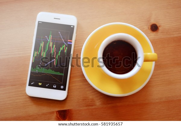 Trader have monitoring Stock market chart on mobile phone in coffee cafe.