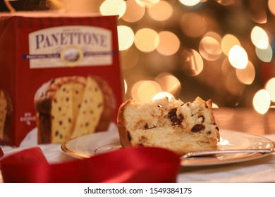 Trader Joe's panettone cake on a gold plate. The box and Christmas tree lights in the background in bokeh. Red ribbon blurred in the front of the photo. — Home, Boston, MA, USA 12/2/2018.