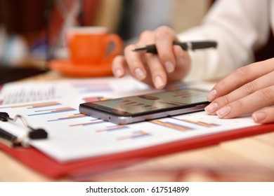 Trader woman hand analyzing income data on mobile phone screen. Close up