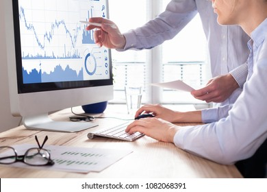 Traders discussing trading strategy for better profit and return on investment (ROI) by analyzing stock market and foreign exchange (forex) charts on computer screen