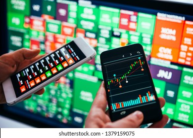 Traders or financial analysts checking the recent stock exchange trends using their smartphones. Selective focus