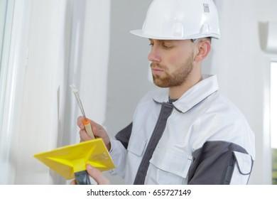 Tradesman filling cracks in wall
