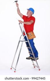 Tradesman installing a light fixture