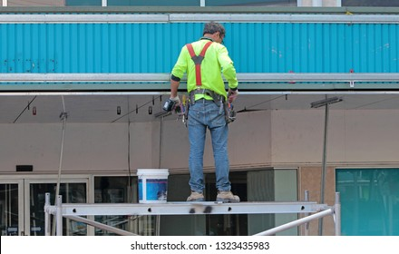 Tradesman on aluminum scaffolding working on shop front awning