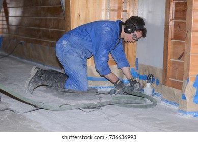 A tradesman polishes the edges of a concrete floor with a small angle grinder after a large grinder has done its job