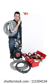 Tradesman posing with a blank sign and his tools