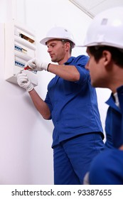 Tradesman repairing a distribution board
