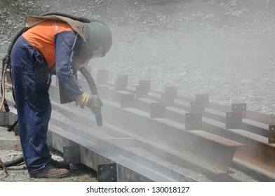 tradesman sandblasting I beams for building project
