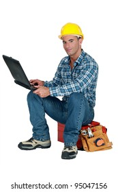 Tradesman sitting on his toolbox and using his laptop