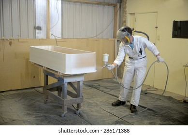 Tradesman spray painting a coffin in a spray booth