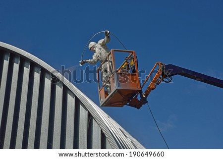Tradesman Spray Painting Roof Industrial Building Stock