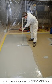 A tradesman spreads an epoxy flooring product in an industrial building. The plastic curtain keeps the job from becoming contaminated.