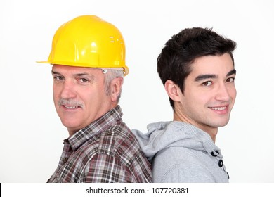 Tradesman standing back to back with his apprentice