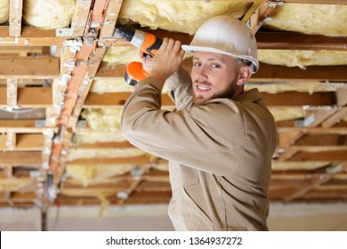 tradesman using drill on wooden framework of ceiling