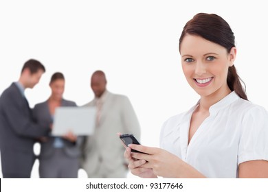 Tradeswoman with cellphone and co-workers behind her against a white background