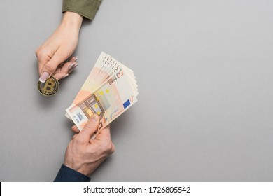 Trading symbol. Bitcoin buy and sell concept, hands holding bitcoin and euro money.