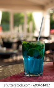 Tradition Summer drink blue mojito with lime mint and ice. Blue background