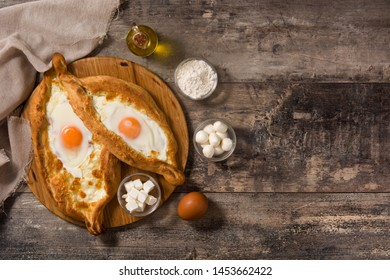 Traditional Adjarian Georgian khachapuri with cheese and egg on wooden table. Top view. Copyspace